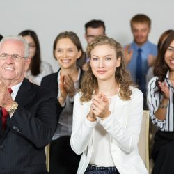 Audience of nine business people looking at speaker, smiling and applauding. One woman in foreground is looking at camera. Front view of audience. Speaker is out of view.